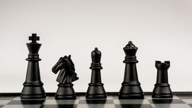 Schwarze schachfiguren an bord. - geschäftsidee für den wettbewerb. - erfolgs- und führungskonzept