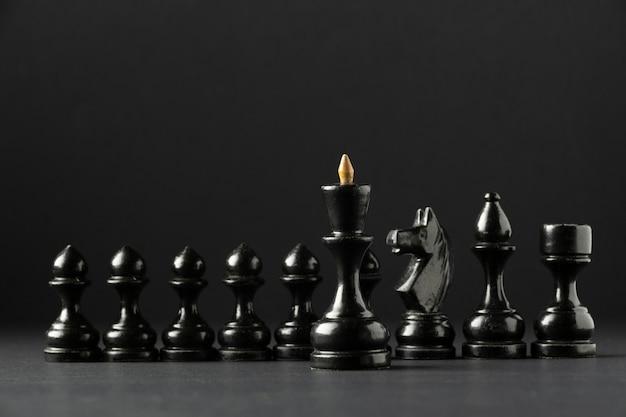 Schwarze schachfiguren auf schwarzem hintergrund