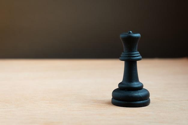 Schwarze schachkönigin mit schwarzem hintergrund