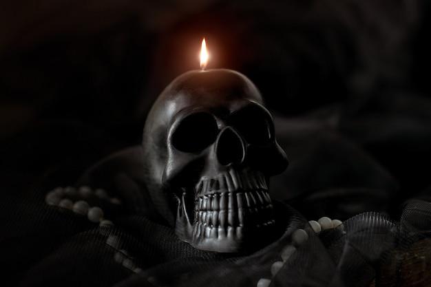 Schwarze schädelkerze auf schwarzem hintergrund. halloween-konzept, mystik, das leben nach dem tod.