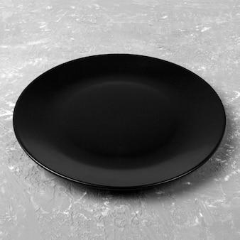 Schwarze schale auf grauem zement