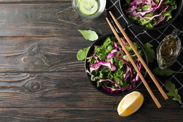 Schwarze schalen mit salat, essstäbchen und handtuch auf hölzernem hintergrund, draufsicht