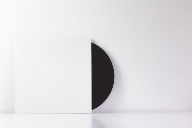 Schwarze schallplatte in der weißen schachtel mit leerzeichen zum schreiben.