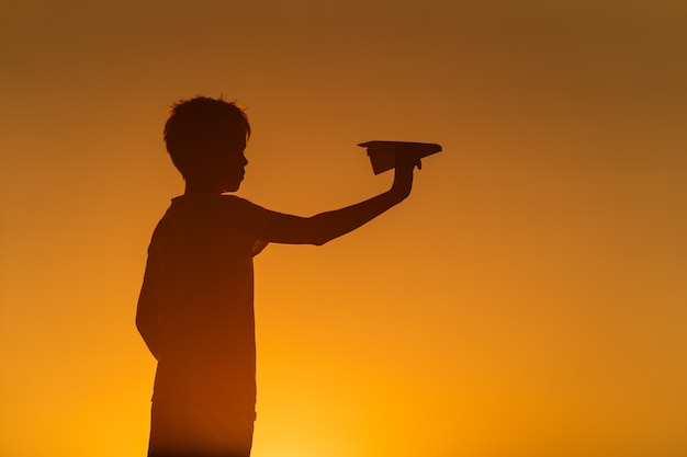Schwarze schattenbild eines jungen, der gegen orange sommersonnenunterganghintergrund steht