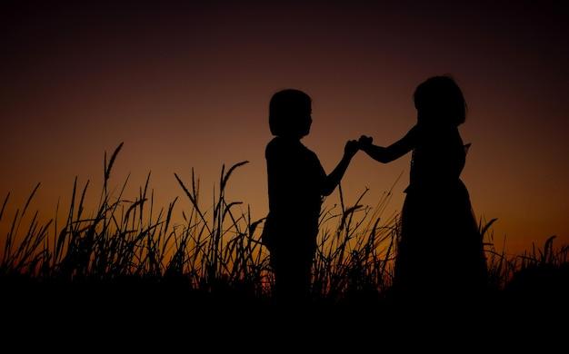 Schwarze schattenbild von zwei asiatischen kleinen mädchen, die auf einem grasfeldhintergrund der herrlichen sonnenuntergänge stehen. das mädchen, das versprechen gibt und handzeichensprache zeigt.