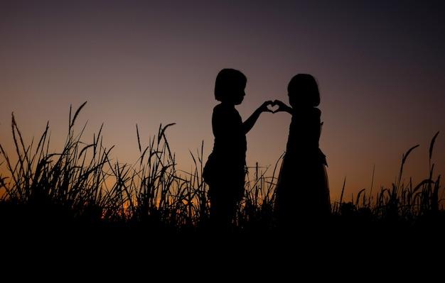 Schwarze schattenbild von zwei asiatischen kleinen mädchen, die auf einem grasfeldhintergrund der herrlichen sonnenuntergänge stehen. das mädchen zeigt liebessymbol mit handzeichensprache.
