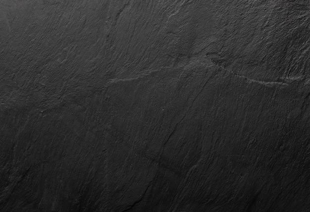 Schwarze schieferstruktur, in der die körnung des minerals zu sehen ist. leerer tisch für käse und andere snacks. copyspace (speicherplatz kopieren).