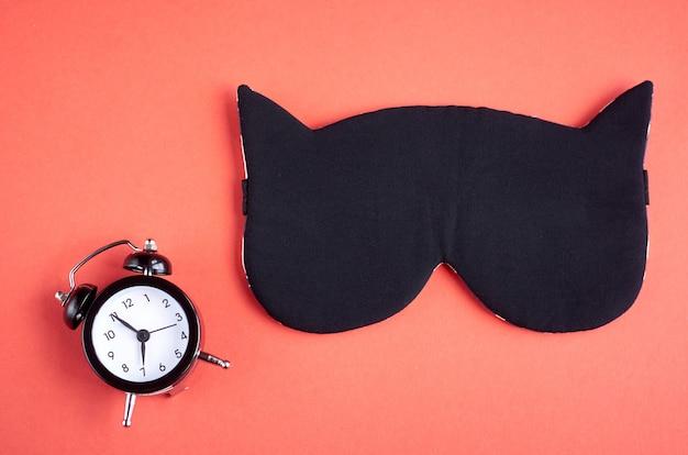Schwarze schlafmaske mit uhr auf rosa zusammensetzung, katzenmaske mit den ohren