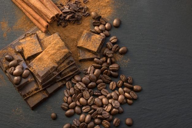 Schwarze schokoladenstücke, zimt und kaffeebohnen, schokoladenstücke aus geriebenem schokoladenpulver auf schieferteller. ansicht von oben.