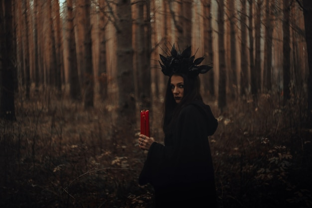 Schwarze schreckliche hexe hält kerzen in ihren händen in einem dunklen wald