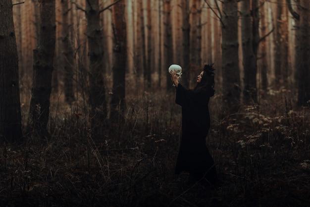 Schwarze schreckliche hexe mit einem schädel in den händen eines toten im wald