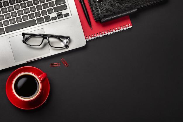 Schwarze schreibtischtabelle mit laptop-computer des leeren bildschirms, notizbuch, maus, tasse kaffee und anderem büro.