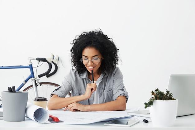Schwarze schülerin oder studentin, die ihre hausaufgabe beendet und fehler in ihren zeichnungen korrigiert