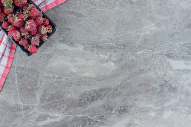 Schwarze schüssel erdbeeren und himbeeren auf einer tischdecke auf marmor.
