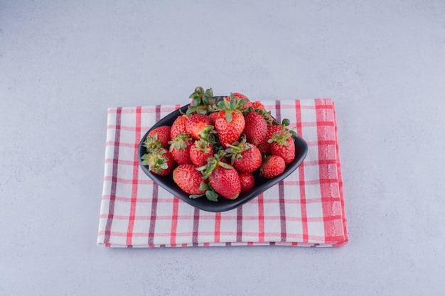 Schwarze schüssel mit einem haufen erdbeeren auf marmorhintergrund.