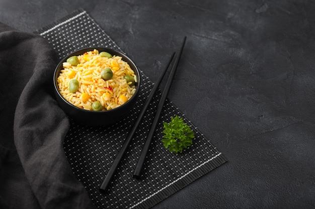Schwarze schüssel mit gekochtem bio-basmatireisreis mit schwarzen stäbchen