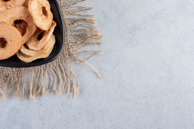 Schwarze schüssel mit gesunden getrockneten apfelringen auf steinhintergrund