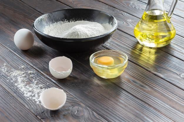 Schwarze schüssel mit mehl. glasflasche mit butter, eiern, eierschale, löffel mit mehl.