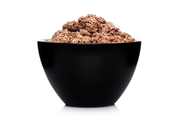Schwarze schüssel mit natürlichem organischem schokoladenmüsli auf weiß