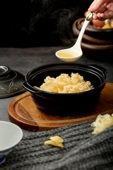 Schwarze schüssel mit suppe auf einer hölzernen platte