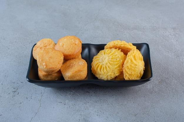 Schwarze schüsseln mit süßen minikuchen und keksen auf blauem hintergrund.