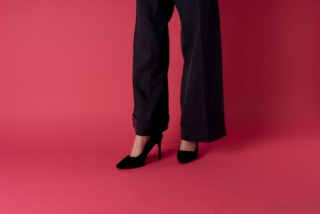 Schwarze schuhe der eleganten beine der schuhe der damen modischen rosa hintergrund