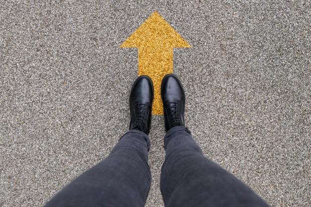 Schwarze schuhe, die auf dem asphaltbetonboden mit gelbem richtungspfeilsymbol stehen. vorwärts, neuanfang und erfolg.. füße schuhe im freien laufen. jugend selphie moderner hipster