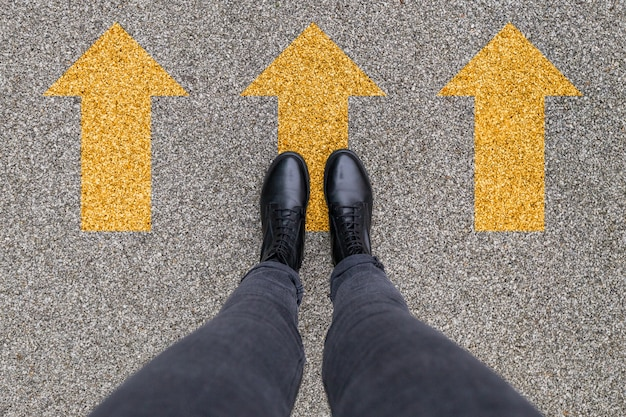Schwarze schuhe stehen auf dem asphaltbetonboden mit drei gelben richtungspfeilen. vorwärts, neuanfang und erfolg.. füße schuhe im freien laufen. jugend selphie moderner hipster