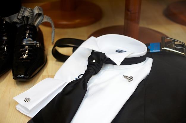 Schwarze schuhe und schwarze krawatte auf einem weißen eleganten hemd