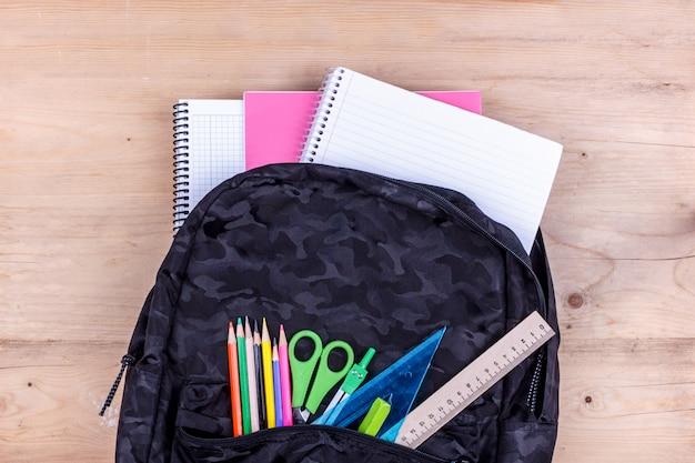 Schwarze schultasche mit einem satz briefpapier für den studenten und einem weißen notizbuch.