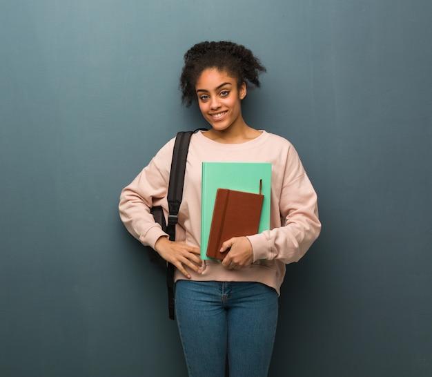 Schwarze schwarze studentin mit den händen auf den hüften. sie hält bücher.