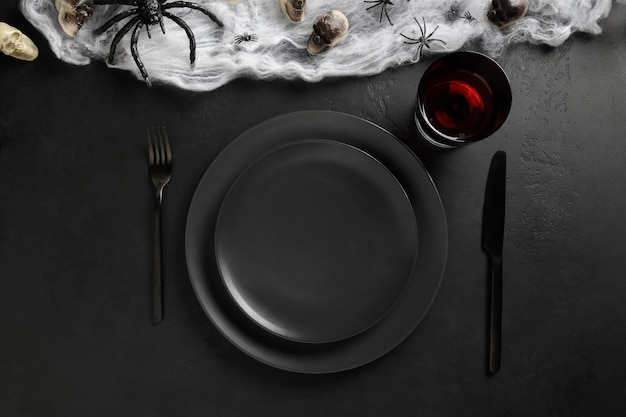 Schwarze schwarze tischdekoration mit spinne, schädel und netz auf schwarzem dunklem tisch