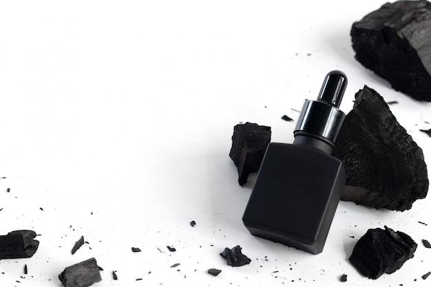 Schwarze serumflasche mit holzkohle auf weißem hintergrund, modellprodukt