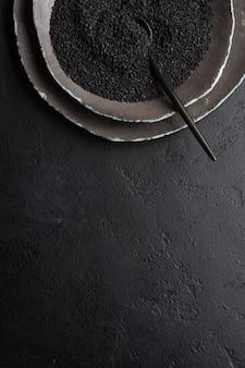 Schwarze sesamsamen in schwarzen keramikplatten auf einem dunklen alten vintage-hintergrund. rustikaler stil. ansicht von oben.