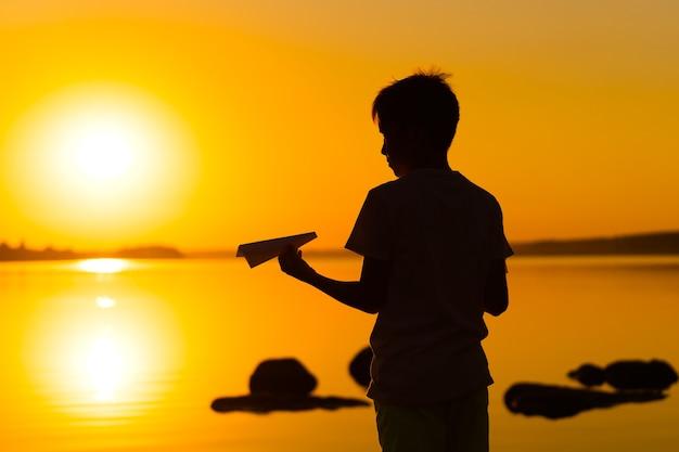 Schwarze silhouette eines jungen, der gegen orange sommersonnenunterganghintergrund steht. hält ein kleines papierflugzeug in den händen. horizontales foto.