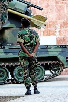 Schwarze soldatfrau, die nahe bei einem gepanzerten raketenfahrzeug steht.