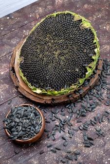 Schwarze sonnenblumenkerne der draufsicht frisch und lecker auf dem braunen schreibtischkorn-sonnenblumenkern-snacköl