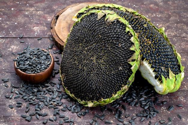 Schwarze sonnenblumenkerne der draufsicht frisch und lecker auf dem braunen schreibtischkorn-sonnenblumenkerngranulat