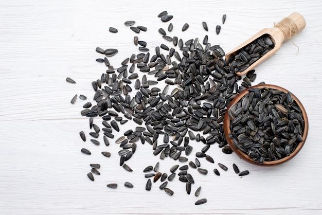 Schwarze sonnenblumenkerne der draufsicht frisch und lecker überall auf dem weißen hintergrundkorn-sonnenblumenkerngranulat