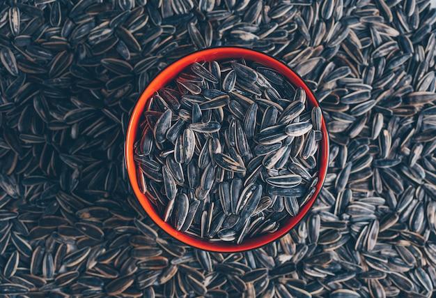 Schwarze sonnenblumenkerne der draufsicht in der schüssel mit samen auf hintergrund. horizontal