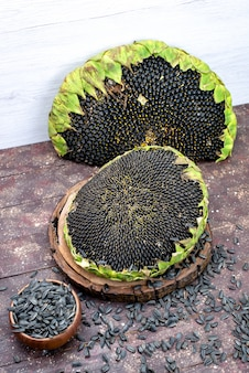 Schwarze sonnenblumenkerne mit draufsicht frisch und lecker auf dem braunen schreibtischkorn-sonnenblumenkern-snack ölig