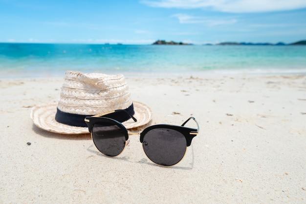 Schwarze sonnenbrille auf dem meereshintergrund. schöner sandstrand als sommer-, reise- und urlaubskonzept. urlaubskonzept.