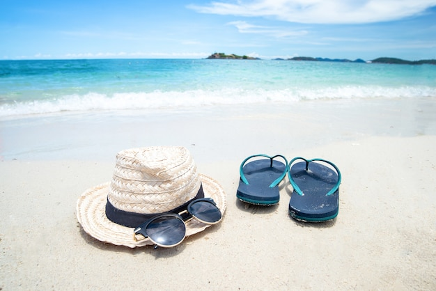 Schwarze sonnenbrille mit strohhut nahe pantoffel auf dem frischen seehintergrund. schöner sandstrand als sommer-, reise- und urlaubskonzept. urlaubskonzept.