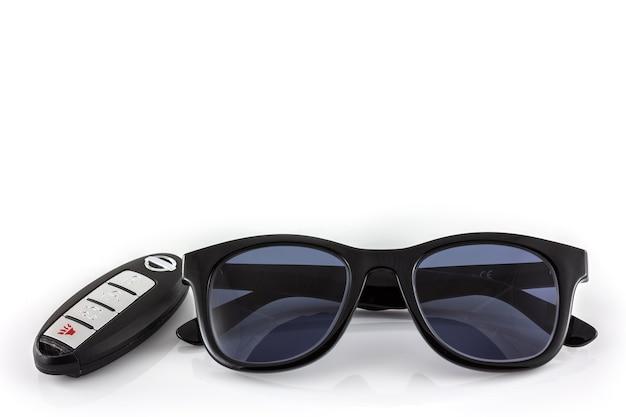 Schwarze sonnenbrille und autoschlüssel im weißen hintergrund