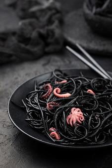 Schwarze spaghetti auf teller mit tintenfisch und stäbchen
