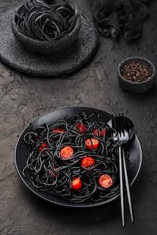 Schwarze spaghetti auf teller mit tomaten