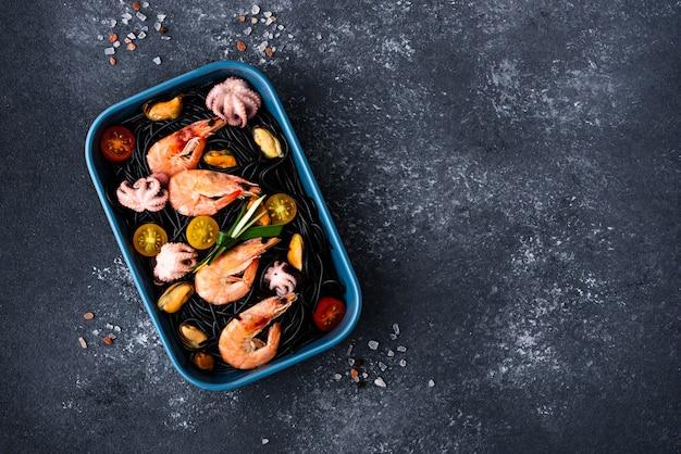 Schwarze spaghetti der draufsicht mit tinten-tintenfisch mit meeresfrüchte-muscheln, garnelen, kraken, tomaten in der blauen platte auf grauem hintergrund mit kopienraum