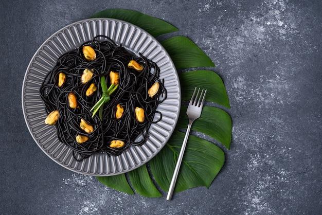 Schwarze spaghetti der draufsicht mit tinten-tintenfisch mit muscheln in grauer platte mit gabel auf grünem blatt auf grauem hintergrund mit kopienraum