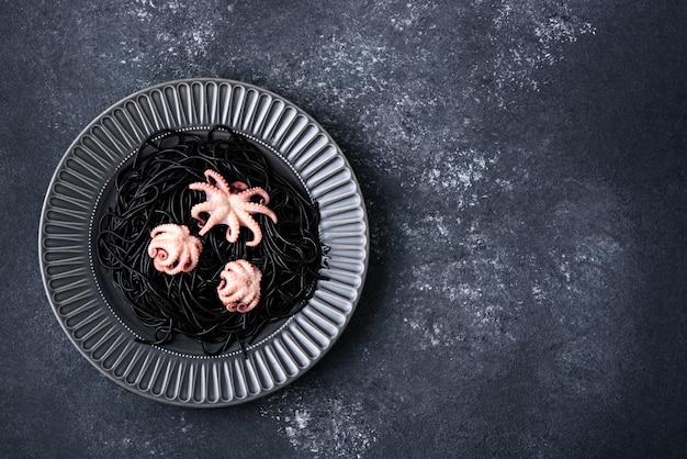 Schwarze spaghetti der draufsicht mit tinten-tintenfisch mit tintenfischen in der grauen platte auf grauem hintergrund mit kopienraum, mediterranes küchenkonzept