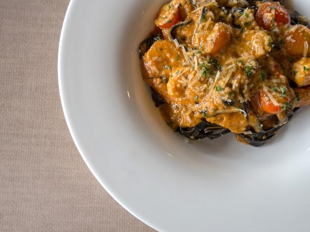 Schwarze spaghetti in tomatensauce mit garnelen, tomaten mit gewürzen und käse bestreuen